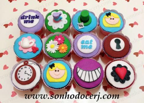 """Cupcakes Alice no País das Maravilhas! Escrito """"Drink me"""" ou """"Eat me""""(E), Xícaras (D), Chapéu do Chapeleiro Maluco 3D (D), Alice - rostinho (E), Bule (C), Trio de Flores (C), Fechadura (C), Relógio do Coelho Branco (E), Sorriso do gato (D), Coração -Rainha de Copas (C)"""