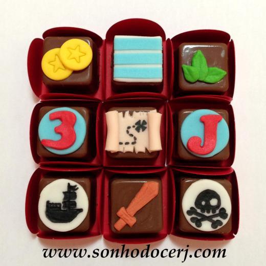 Bombons Modelados Jake e os Piratas! Moedas (2), Listras (2), Folhinhas (2), Número com fundo círculo (2), Mapa do tesouro (3), Letra com fundo círculo (2), Navio Pirata (5), Espada (4), Caveira (5)